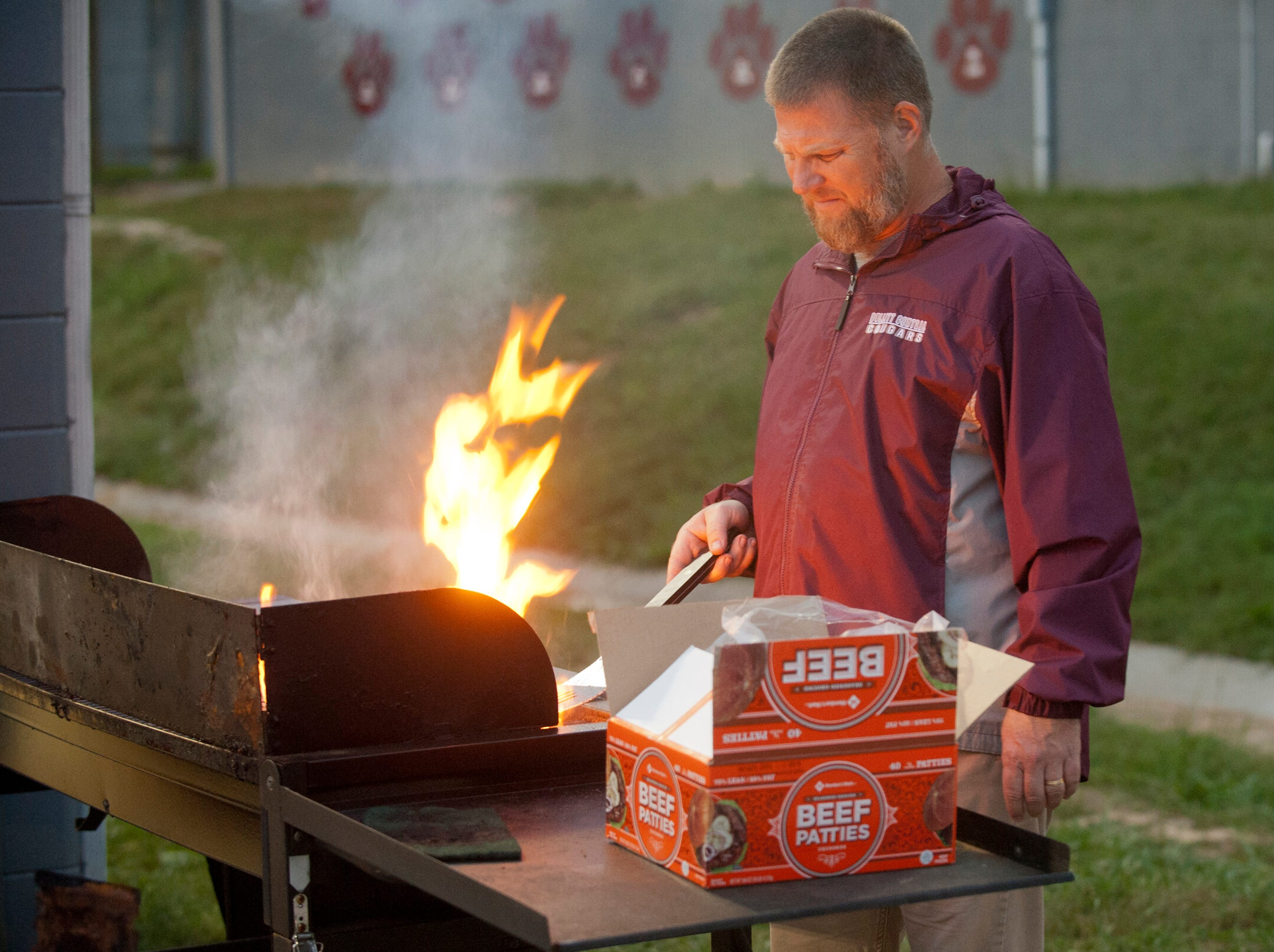 "Bulitt Central Andy Shank who's son, Lucas, is a senior on the baseball squad, cooks up burgers during the football game against South Oldham. He was helping to raise funds for ""Project Grad,"" an in-school seniors celebratory event. Oct. 12, 2018"