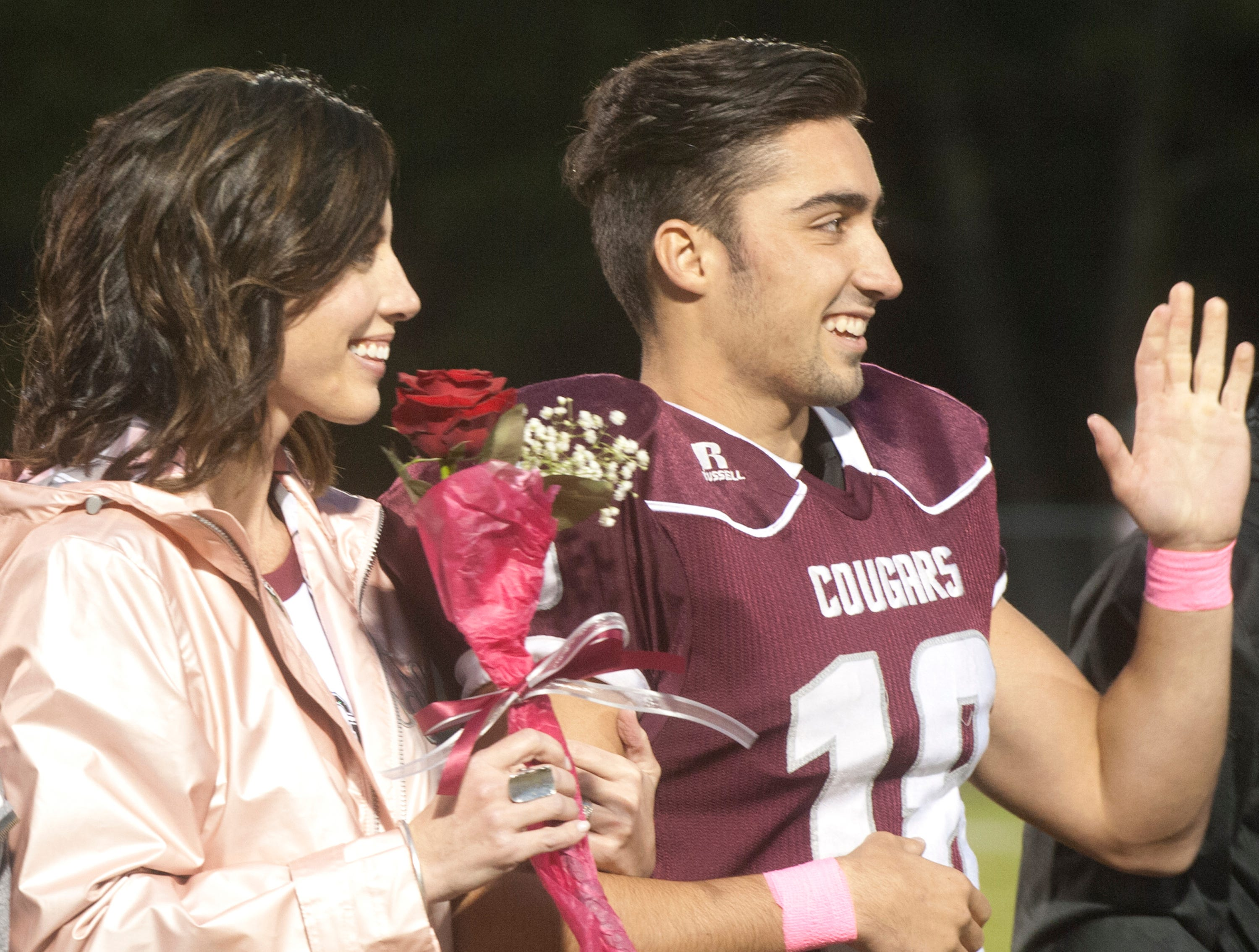"Bullitt Central's Daylin Huff waves at the crowd with his mother, Dara on his arm as they are introduced during ""Seniors"" night  prior to the start of their game against South Oldham. Oct. 12, 2018"