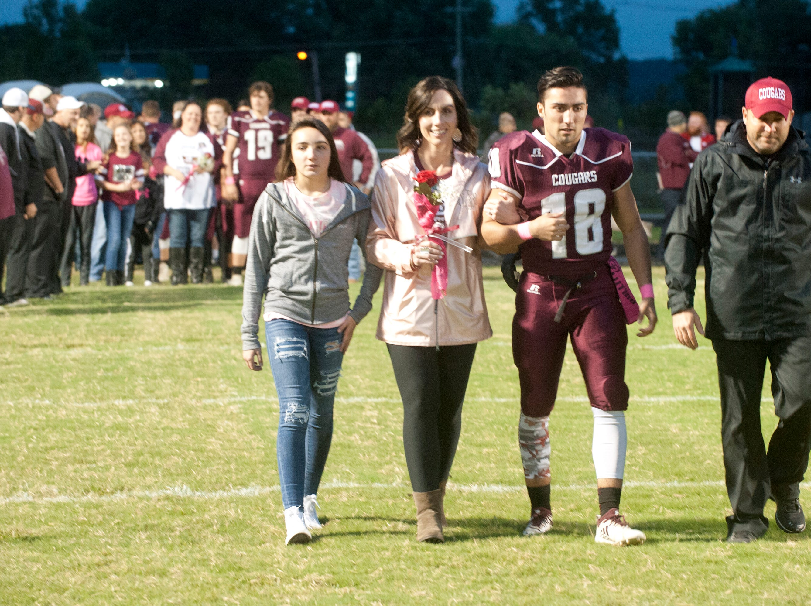 "Bullitt Central's Daylin Huff walks onto the field with his mother, Dara, his father, Devin, and his sister, Presley, 14, at left, as they are introduced during ""Seniors"" night  prior to the start of their game against South Oldham. Oct. 12, 2018"