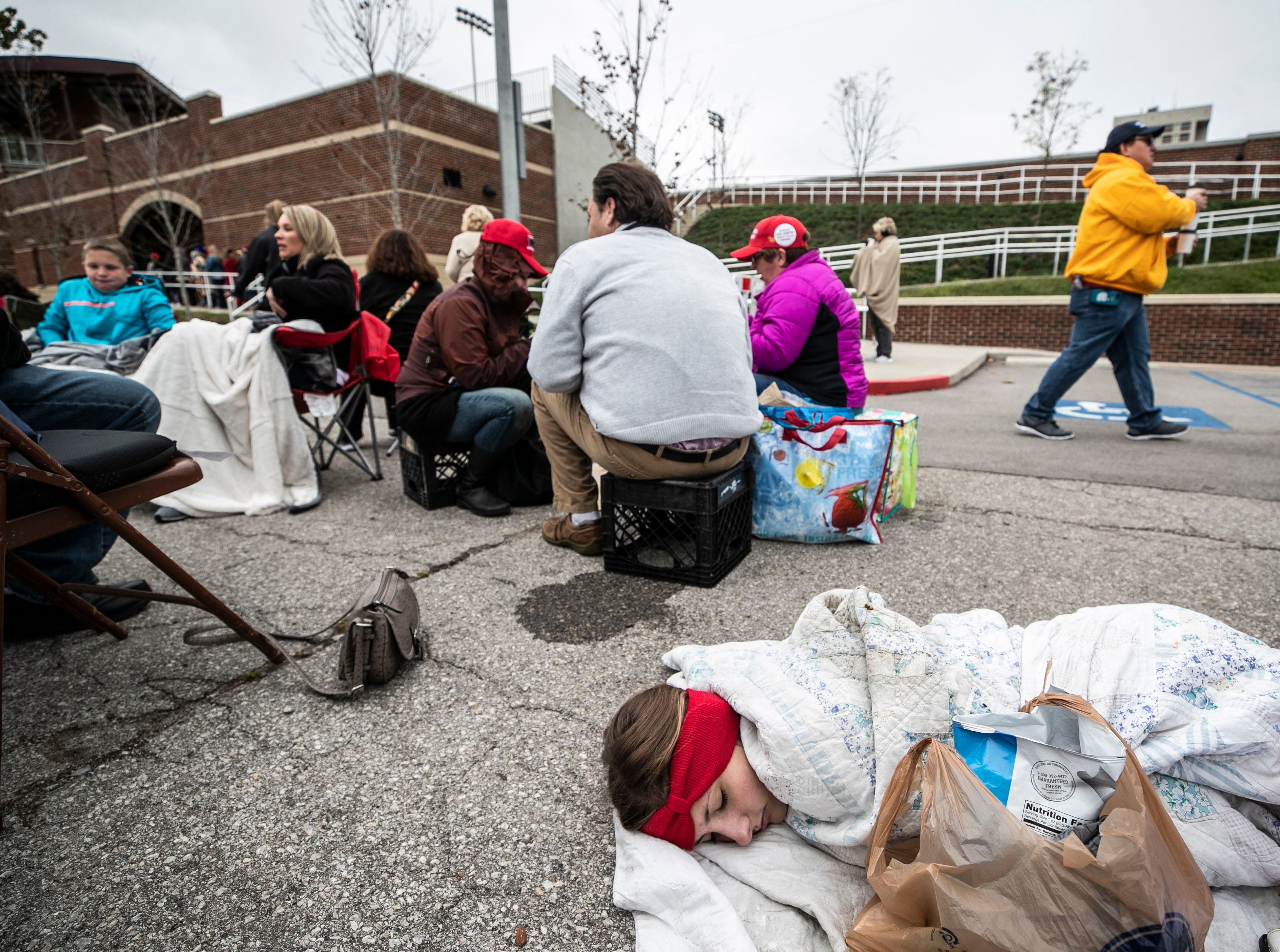 Seventeen-year-old Lexi Lockard sleeps wrapped up in a blanket in a parking lot outside the Alumni Coliseum for the speech of President Donald Trump Saturday night.