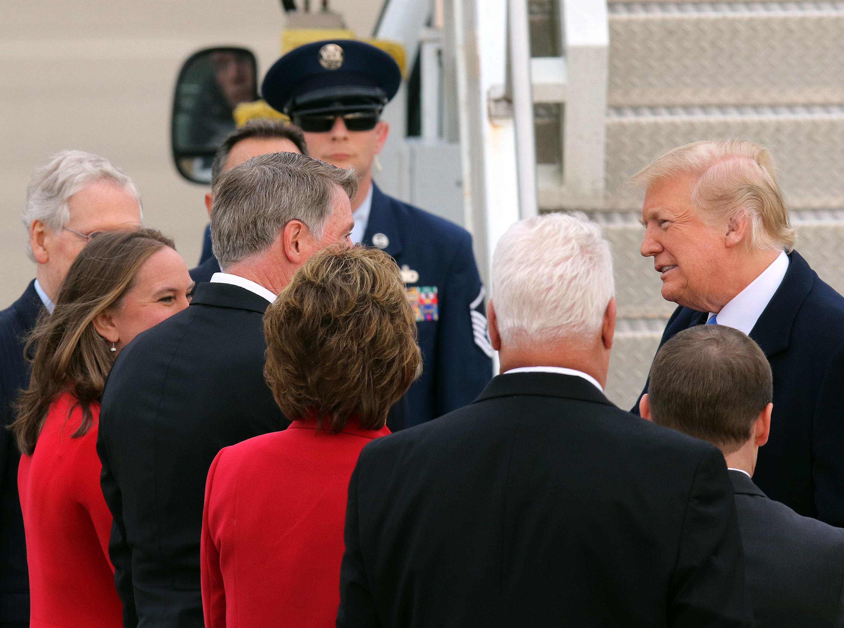 President Trump, right, greets dignitaries near Air Force One after arriving at Bluegrass Airport in Lexington, Oct. 13, 2018.