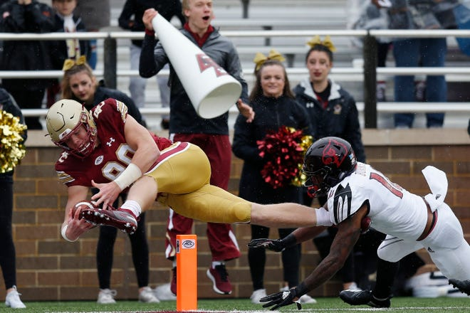 Boston College tight end Hunter Long (80) extends for a touchdown against Louisville cornerback Rodjay Burns (10) during the first half of an NCAA college football game in Boston, Saturday, Oct. 13, 2018.