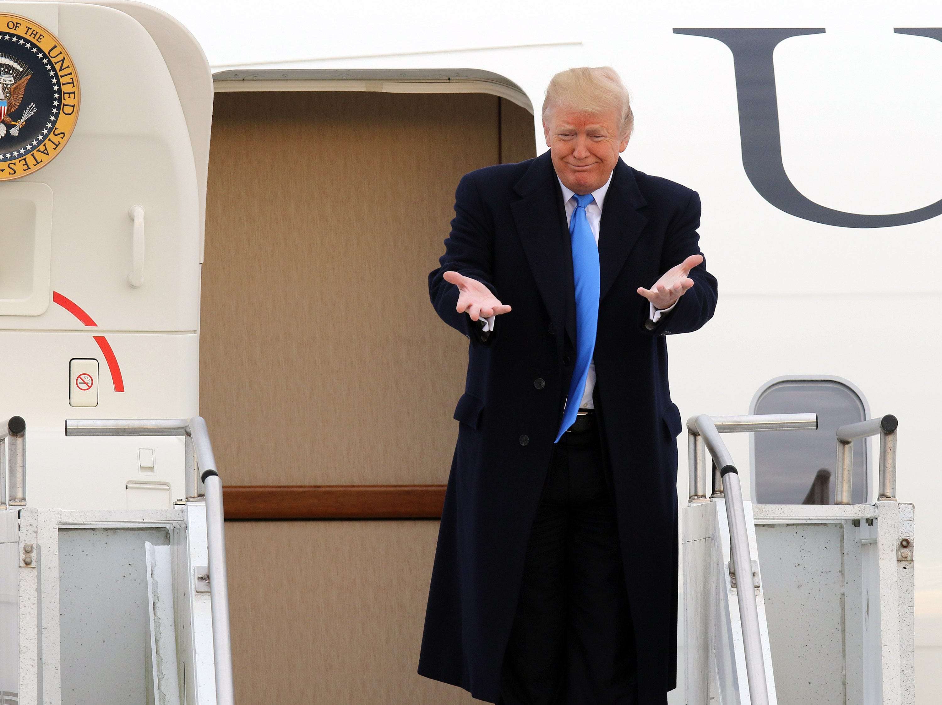 President Trump gestures towards dignitaries from outside Air Force One arrives at Bluegrass Airport in Lexington, Oct. 13, 2018.