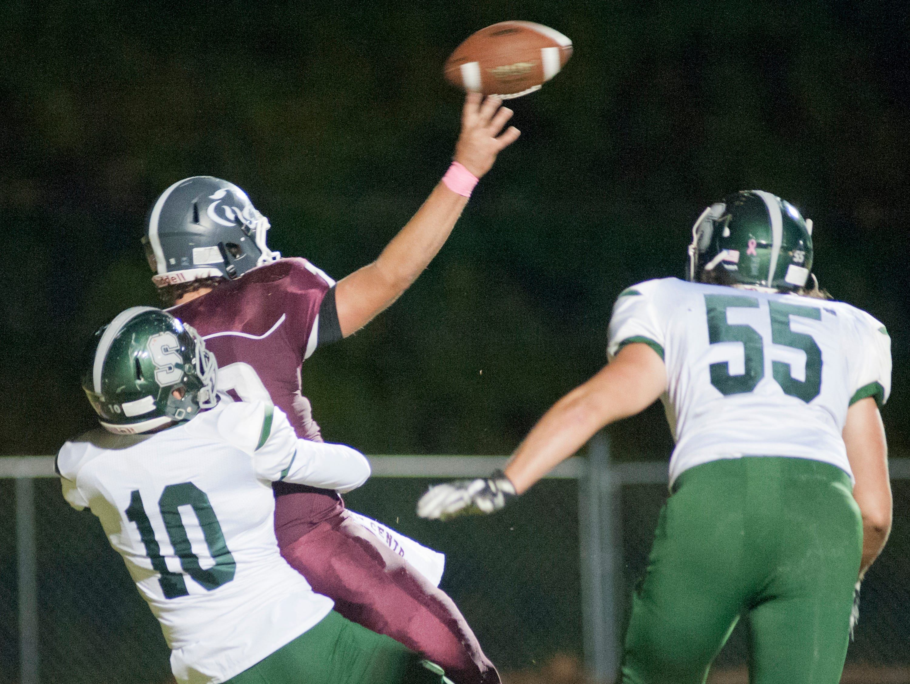 In the end sone, South Oldham linebacker Cade White wraps his arms around Bullitt Central quarterback Jacob Robertson but Robertson is able to get the ball off. At right is South Oldham defensive lineman Jack Harold. Oct. 12, 2018