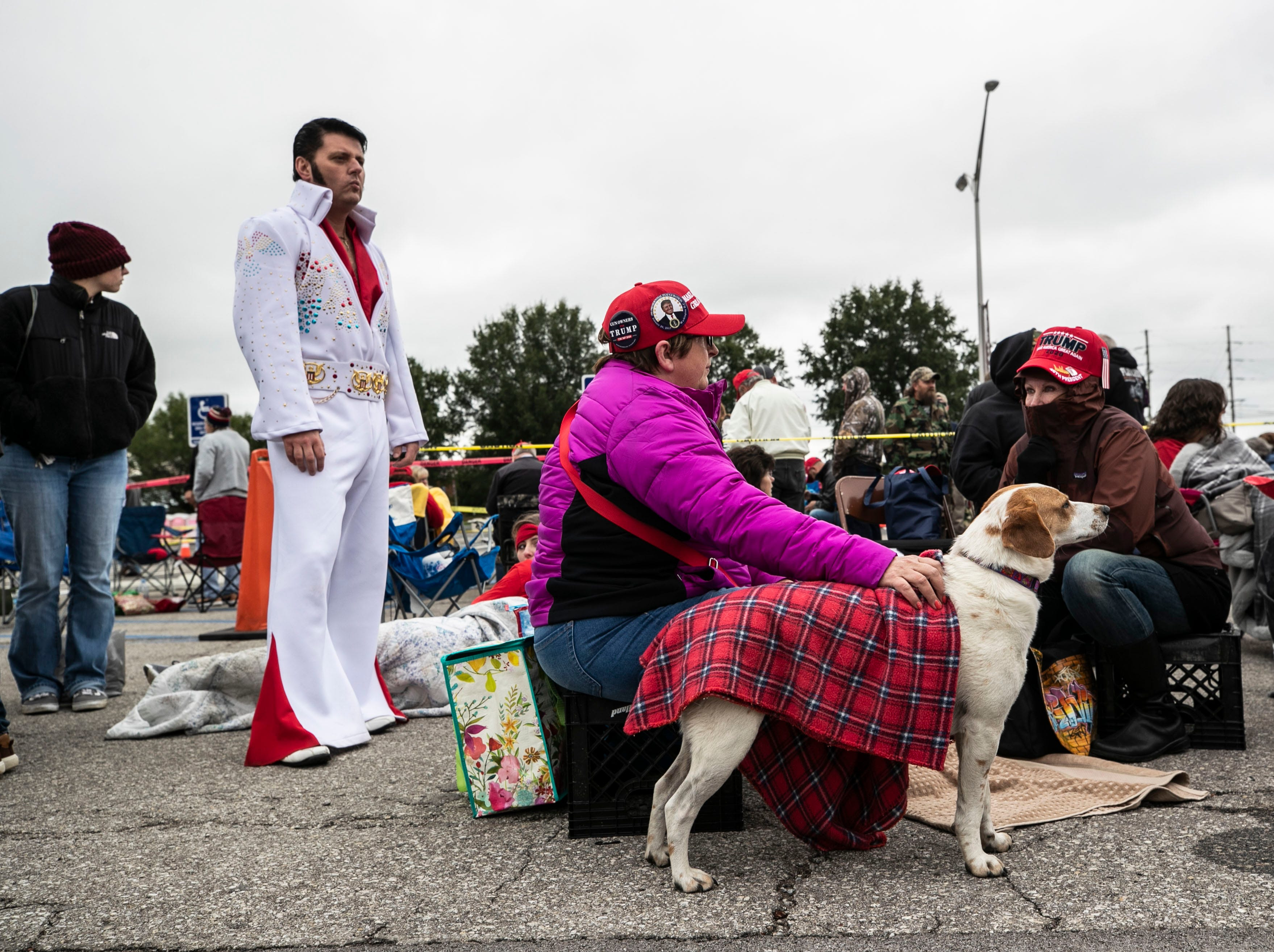 Elvis impersonator Barry Lockard waits with others -- some who brought pets -- in a parking lot outside the Alumni Coliseum for the speech of President Donald Trump Saturday night.