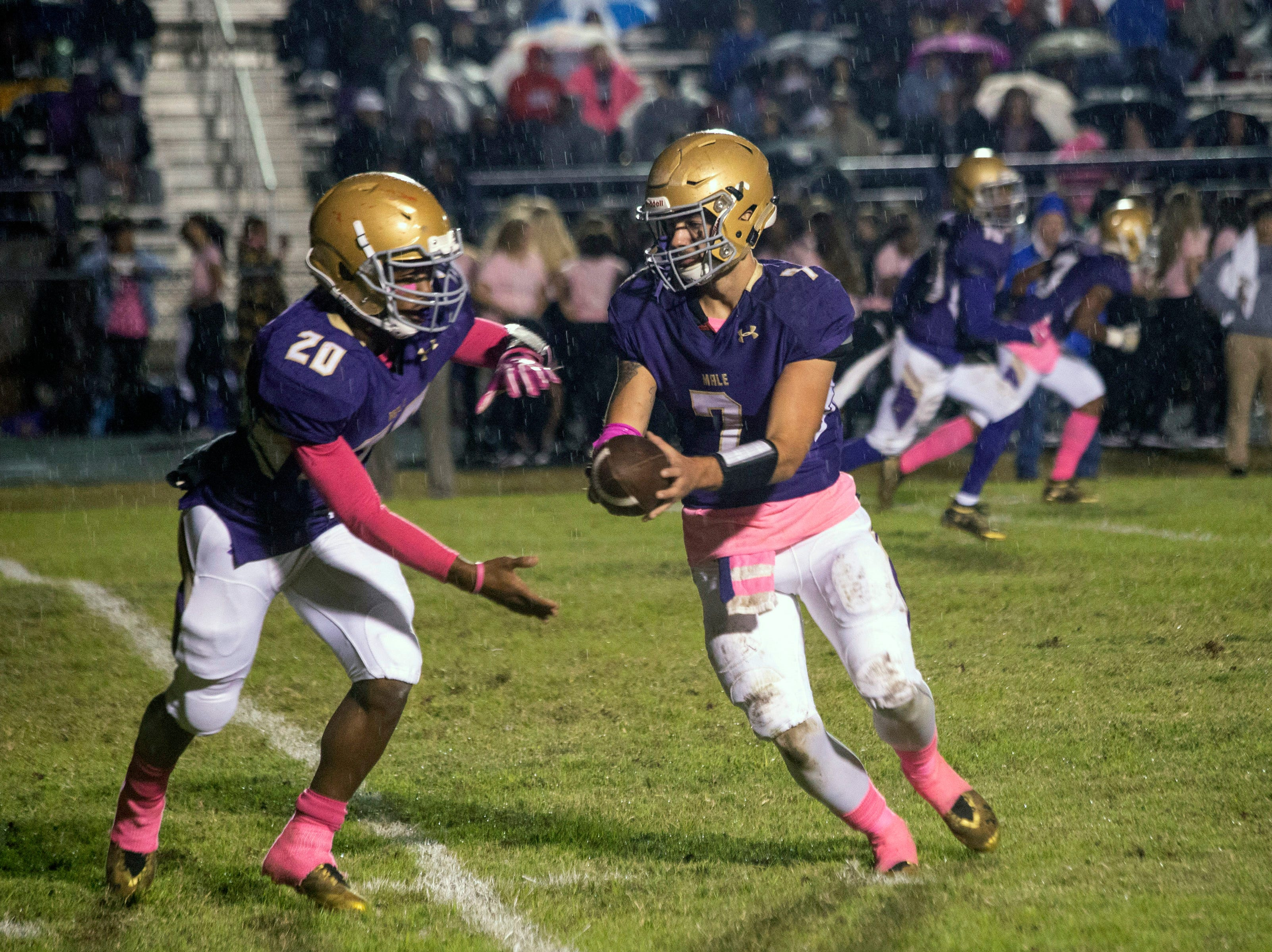 Male quarterback Garrett Dennis hands the ball off to Tony Mosely against St. X on Friday. Oct. 12, 2018