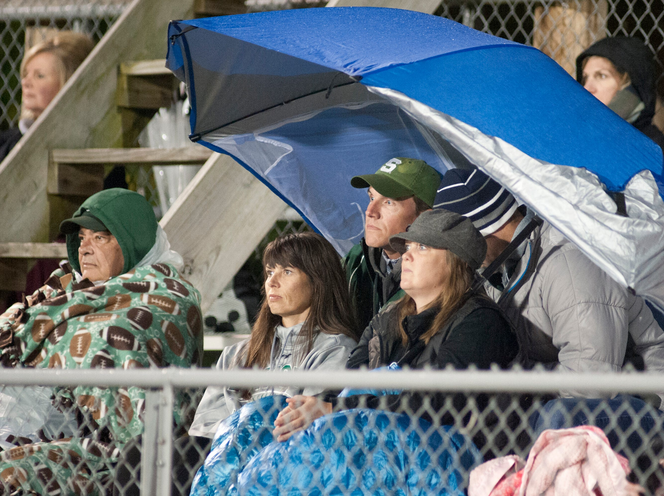 South Oldham fans huddle under blankets and umbrellas to watch their team play. Oct. 12, 2018