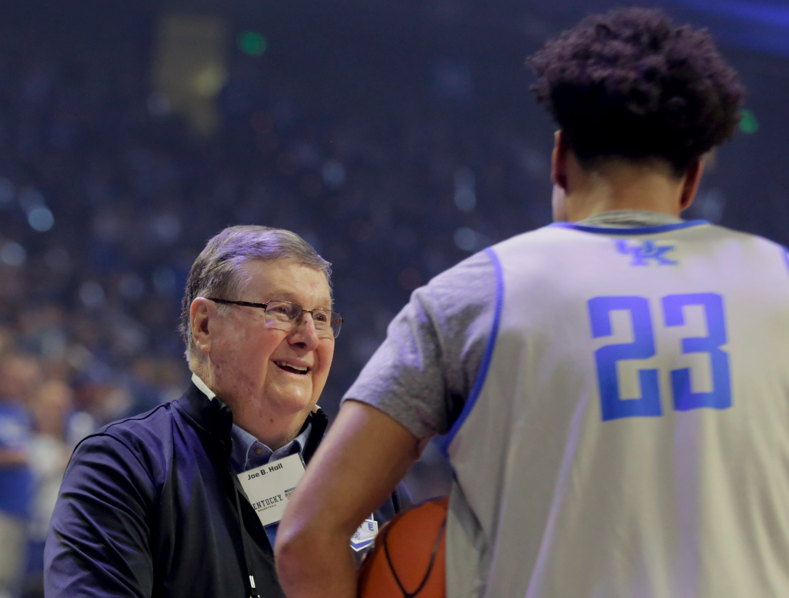 Kentucky legend Joe B. Hall shakes hands with current player EJ Montgomery during Big Blue Madness in Lexington, Kentucky.