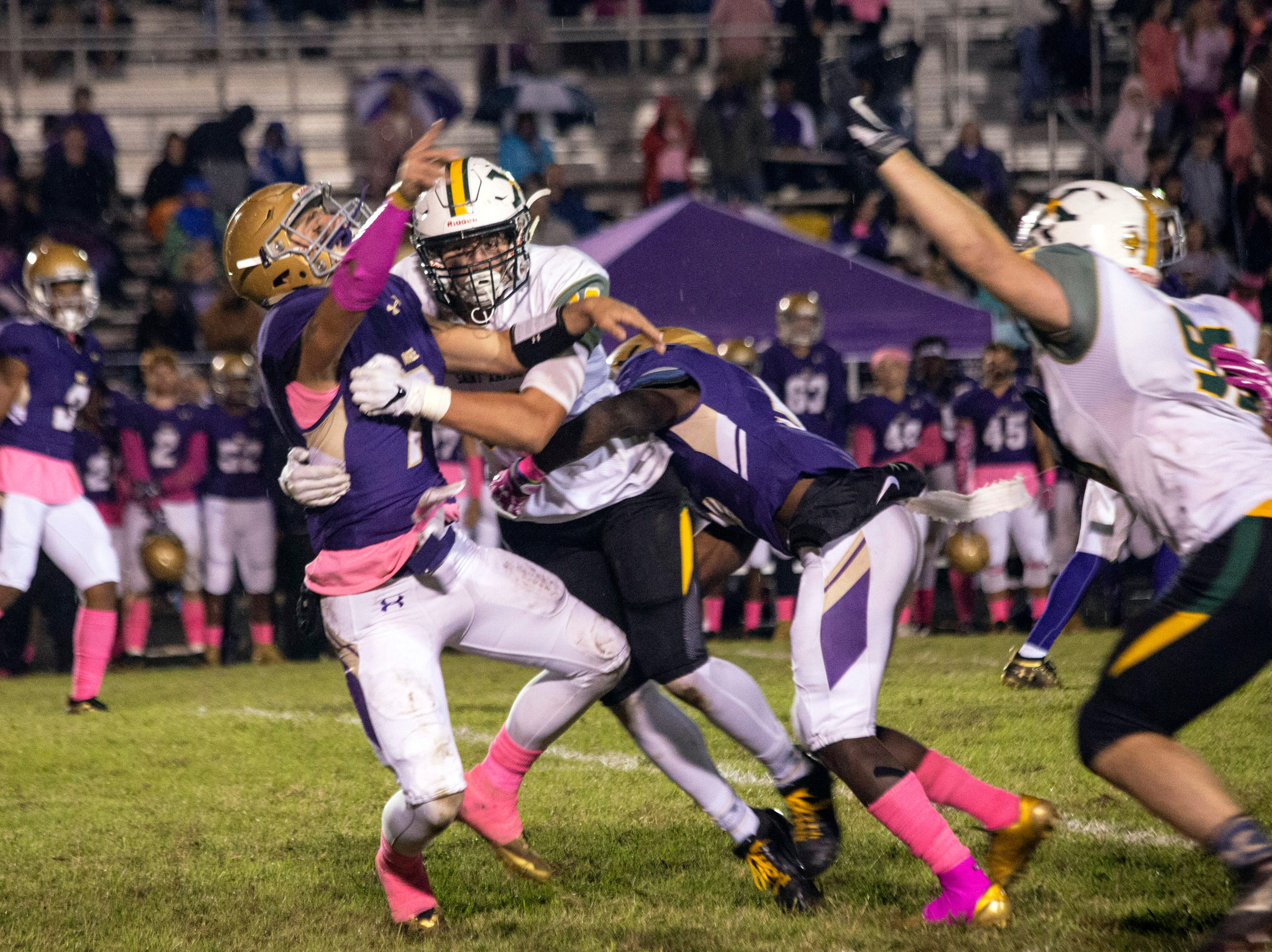 Male quarterback Garrett Dennis is pounded by the St. X defense resulting in a pick-6 touchdown. Oct. 12, 2018