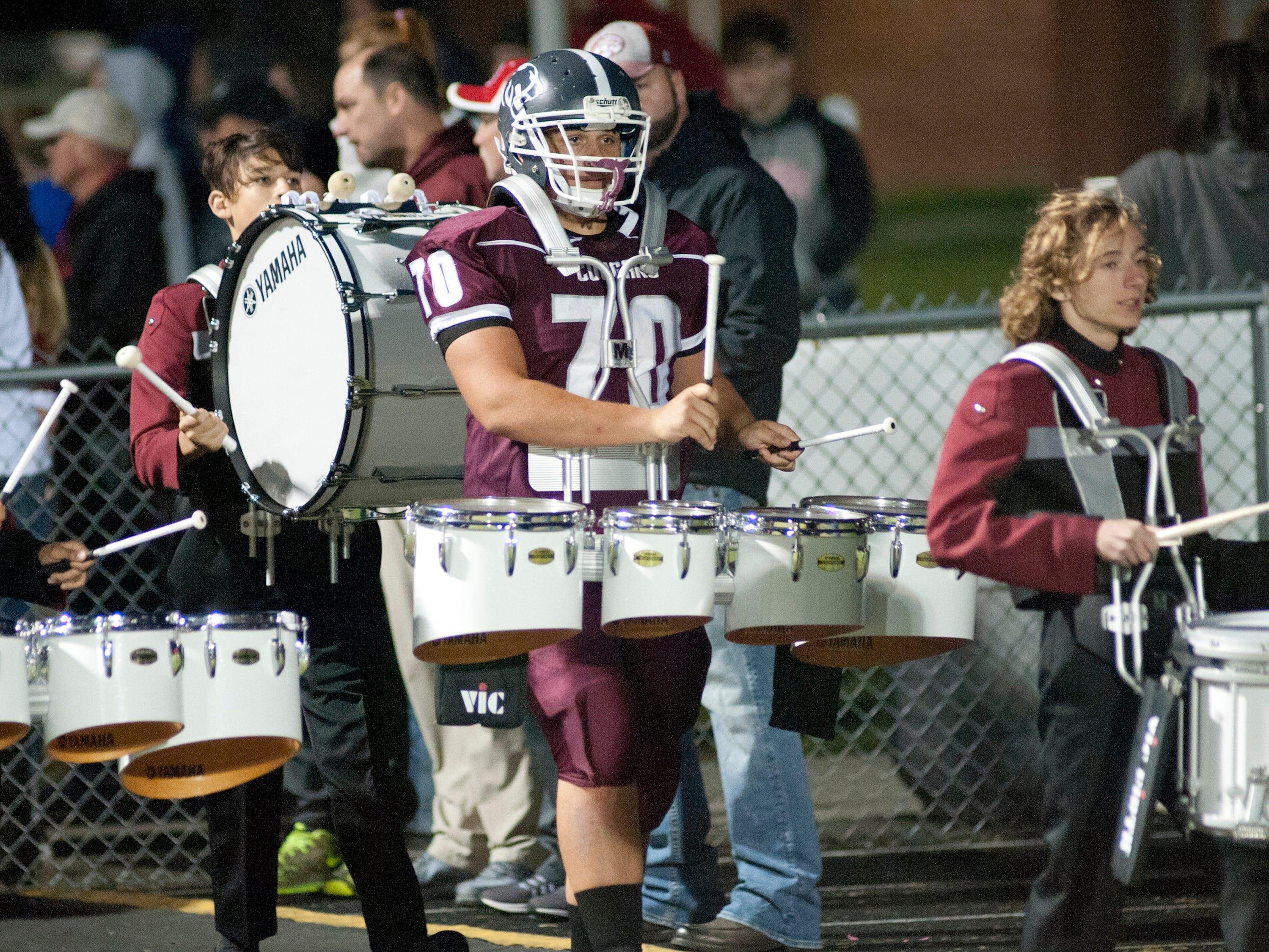 Bullitt Central offensive lineman Kaleb Adams plays the drums in the school marching band as they lead the team onto the field. Oct. 12, 2018