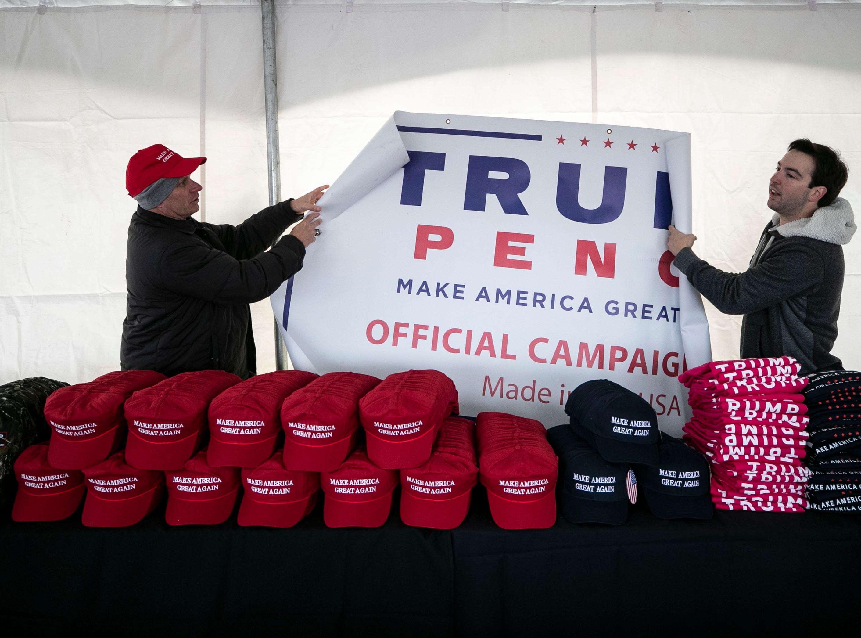 Trump supporters work to hang a sign in a tent selling Donald Trump merchandise before the President arrives to speak in Alumni Coliseum at Eastern Kentucky University. Only credit cards were being accepted.