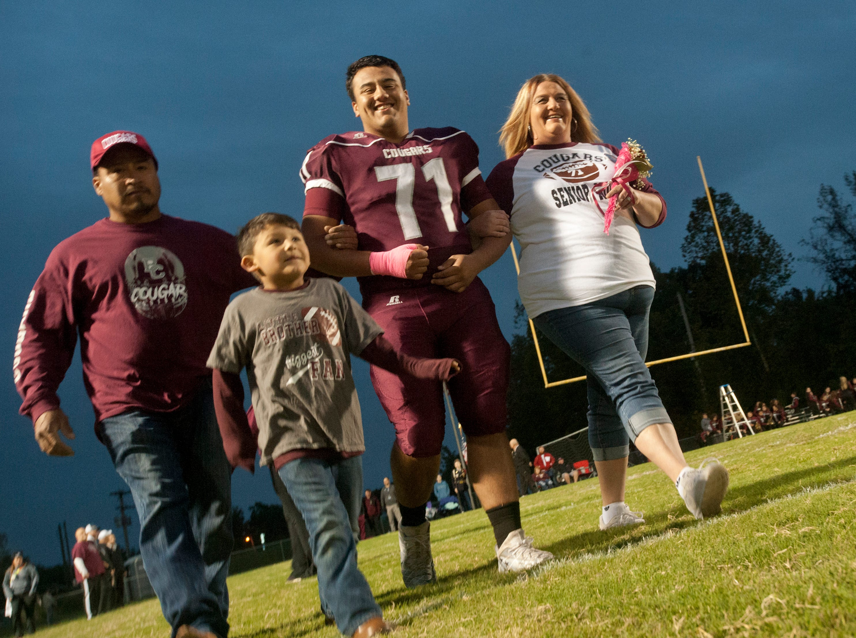 "Bullitt Central offensive lineman Alex Perez walks onto the field with his family, father Miguel, left, mother Rebecca, right, and brother Lukas, age 5, central left, during ""Seniors"" night prior to the start of the game against South Oldham. Oct. 12, 2018"