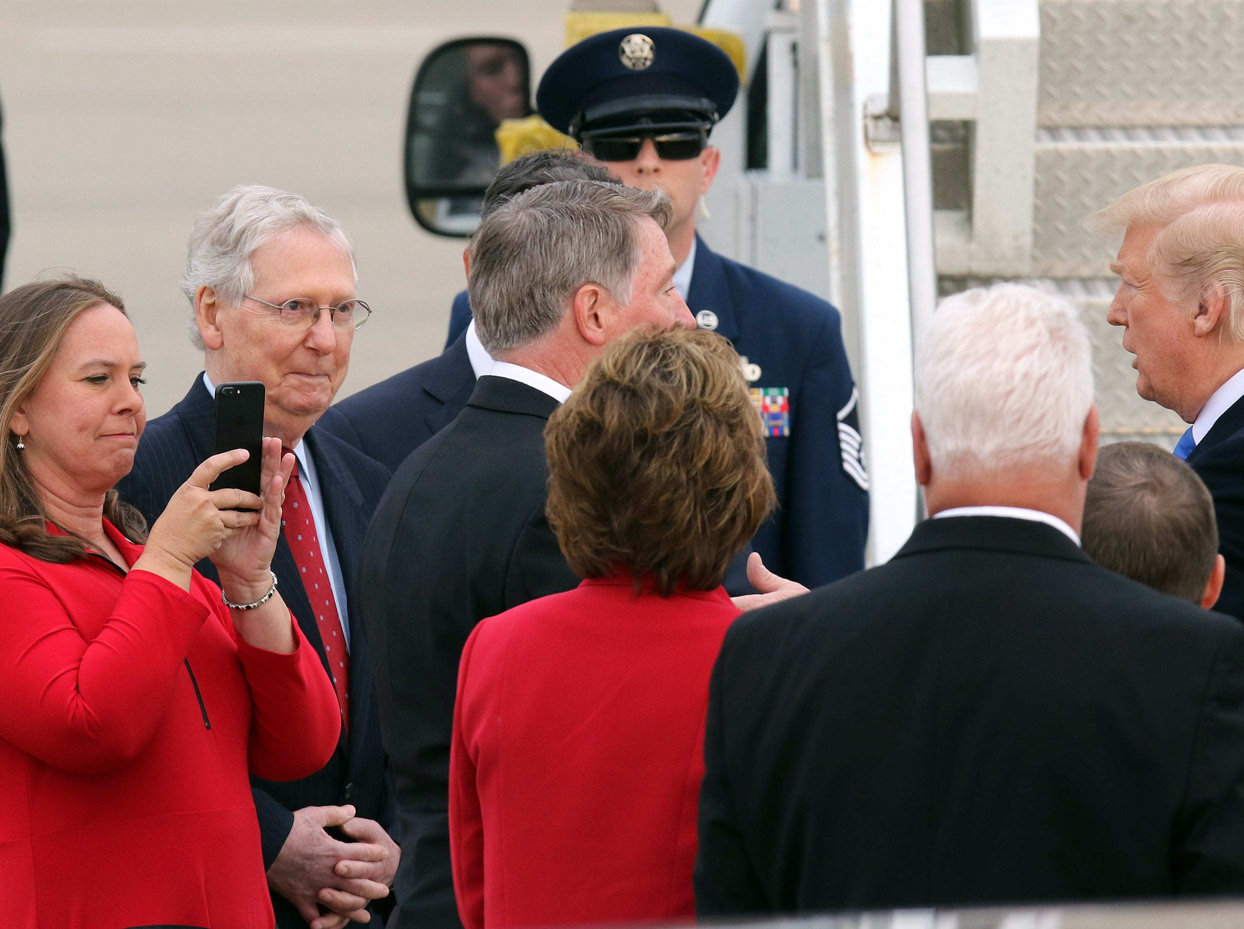 President Trump, right, greets dignitaries as State Rep. Suzanne Miles, left, takes a photo and Sen. Mitch McConnell looks on near Air Force One at Bluegrass Airport in Lexington, Oct. 13, 2018.