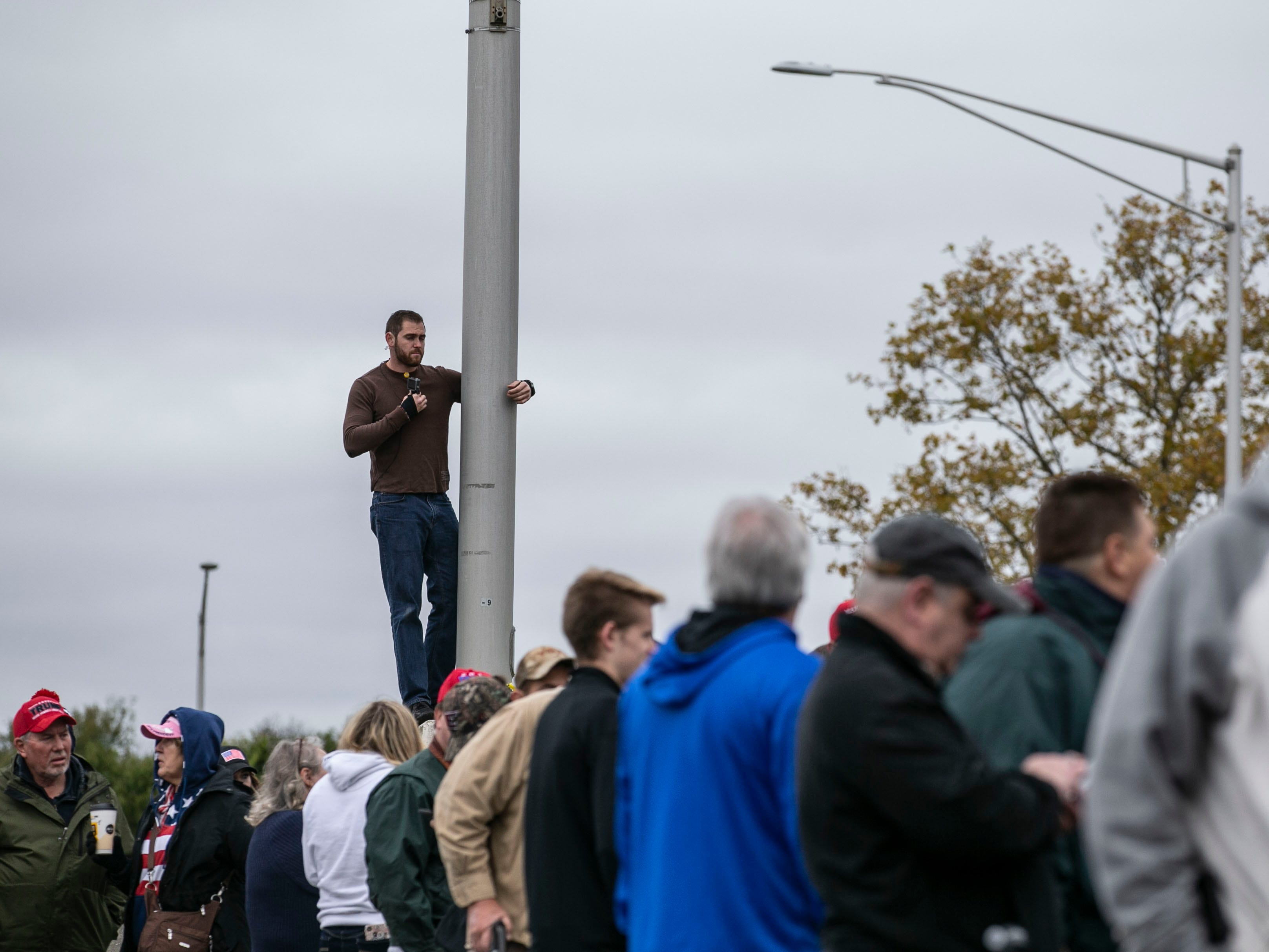 As lines grew, one man tried to get a better look of the crowd from a pole while waiting in a parking lot outside the Alumni Coliseum for the speech of President Donald Trump later Saturday night.