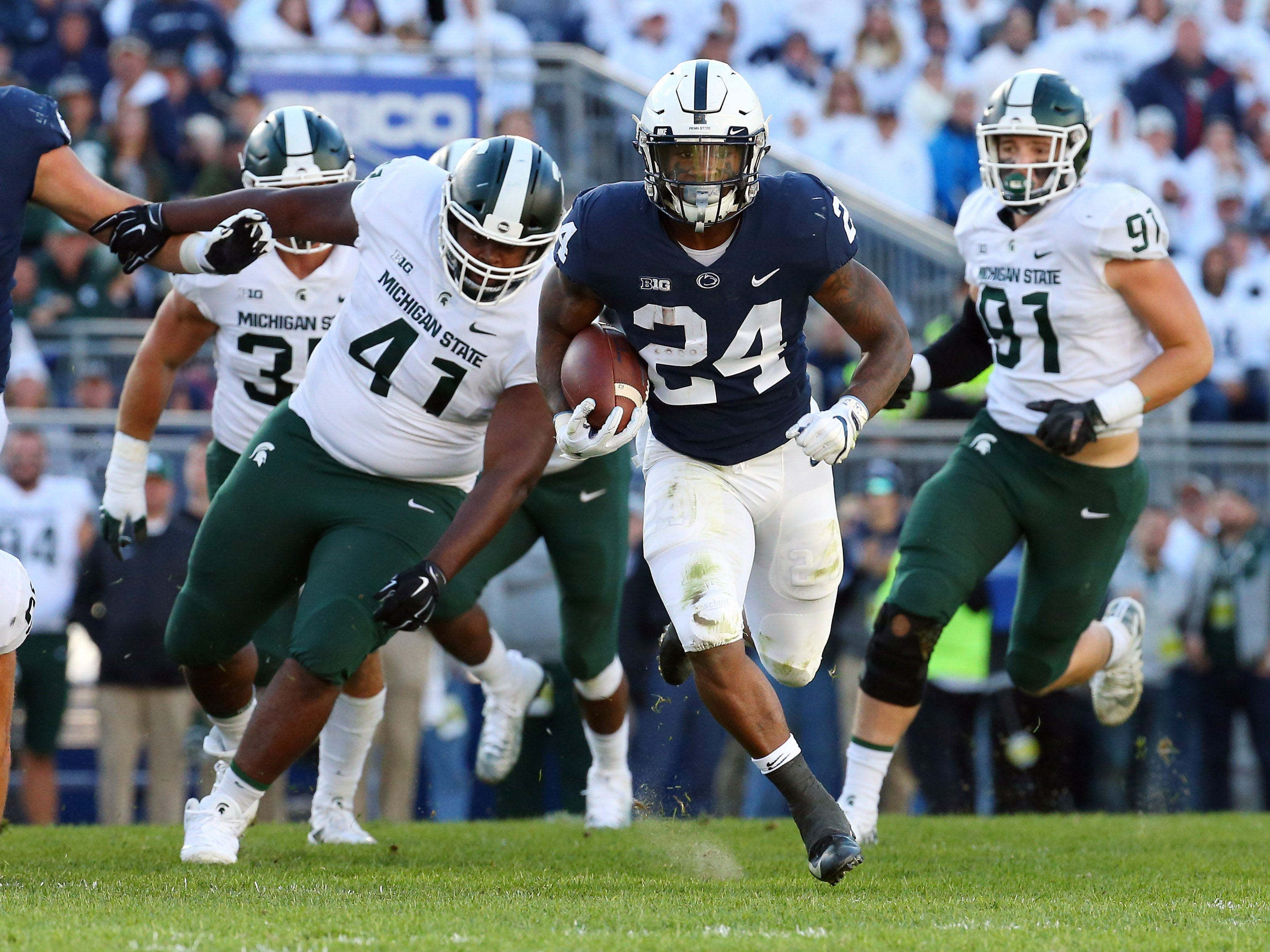 Penn State Nittany Lions running back Miles Sanders (24) runs with the ball past Michigan State Spartans defensive tackle Gerald Owens (41) during the second quarter at Beaver Stadium.