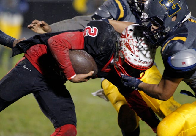 Sexton's Jackson Barnes, left, is stopped by Eastern's Santana Hernandez-Ortiz, Friday, Oct. 12, 2018, in Lansing, Mich. Sexton won 27-8.