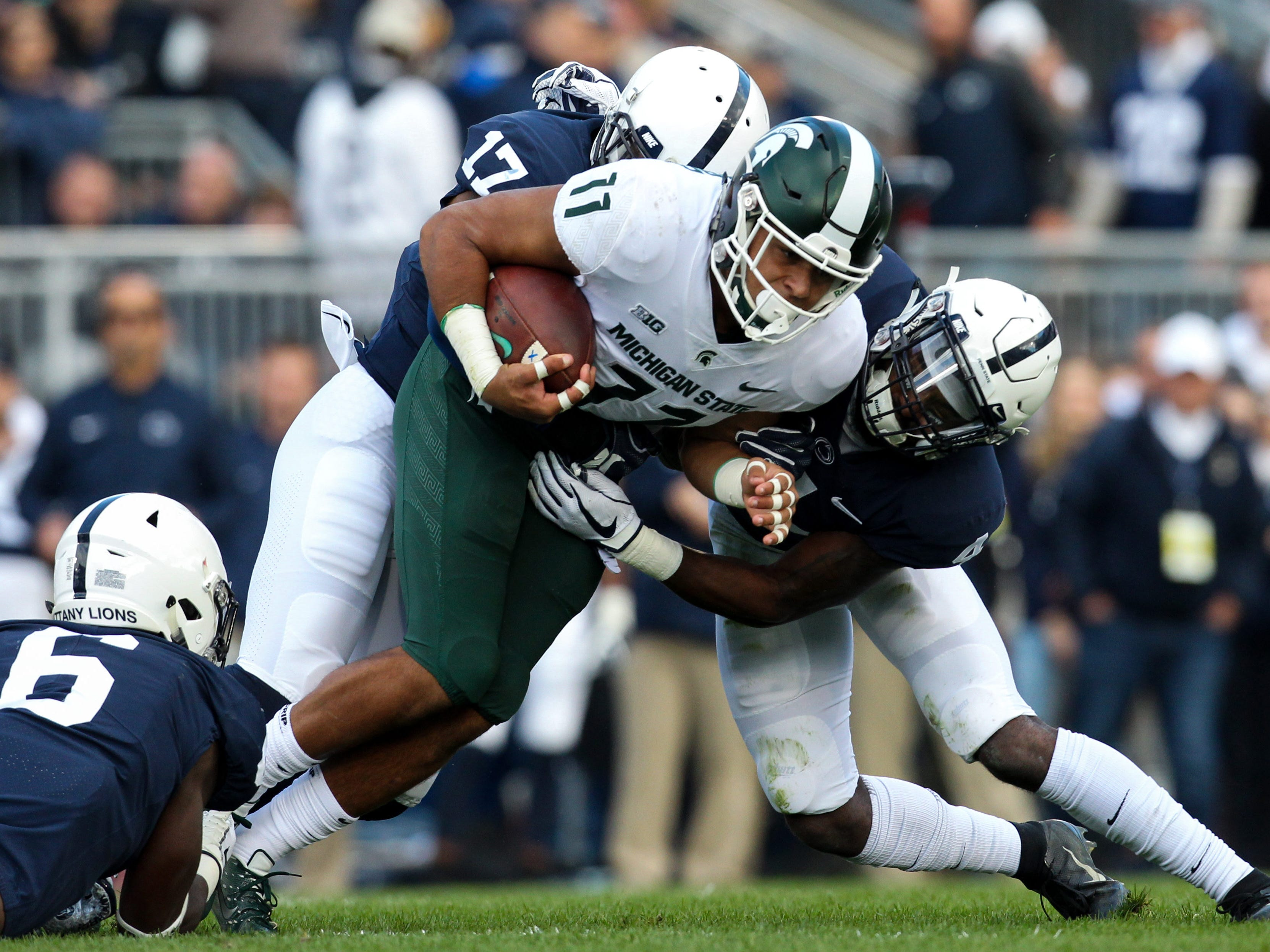 Michigan State Spartans running back Connor Heyward (11) runs with the ball as Penn State Nittany Lions safety Nick Scott (4) attempts a tackle during the first quarter at Beaver Stadium.