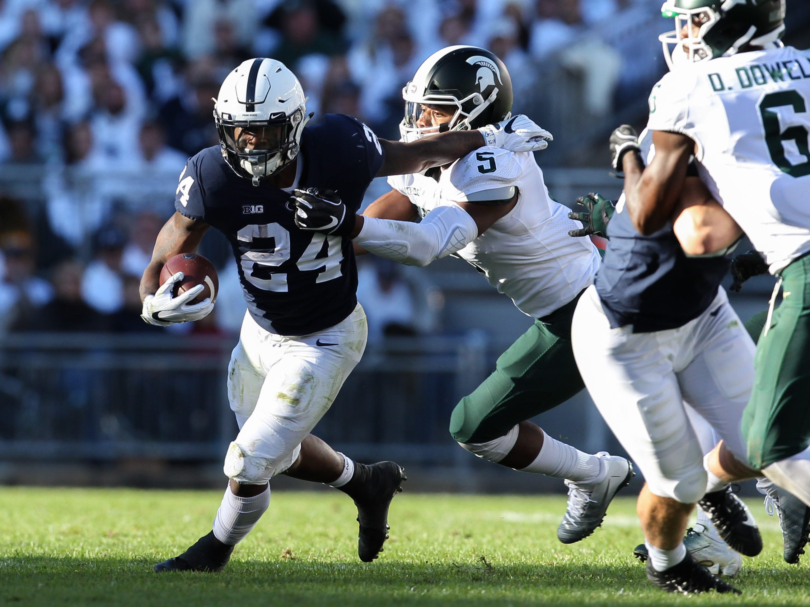 Penn State Nittany Lions running back Miles Sanders (24) runs with the ball while trying to avoid a tackle from Michigan State Spartans linebacker Andrew Dowell (5) during the second quarter at Beaver Stadium. Mandatory Credit: