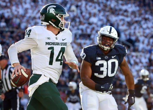 Michigan State Spartans quarterback Brian Lewerke (14) runs with the ball as Penn State Nittany Lions defensive tackle Kevin Givens (30) defends during the second quarter at Beaver Stadium.