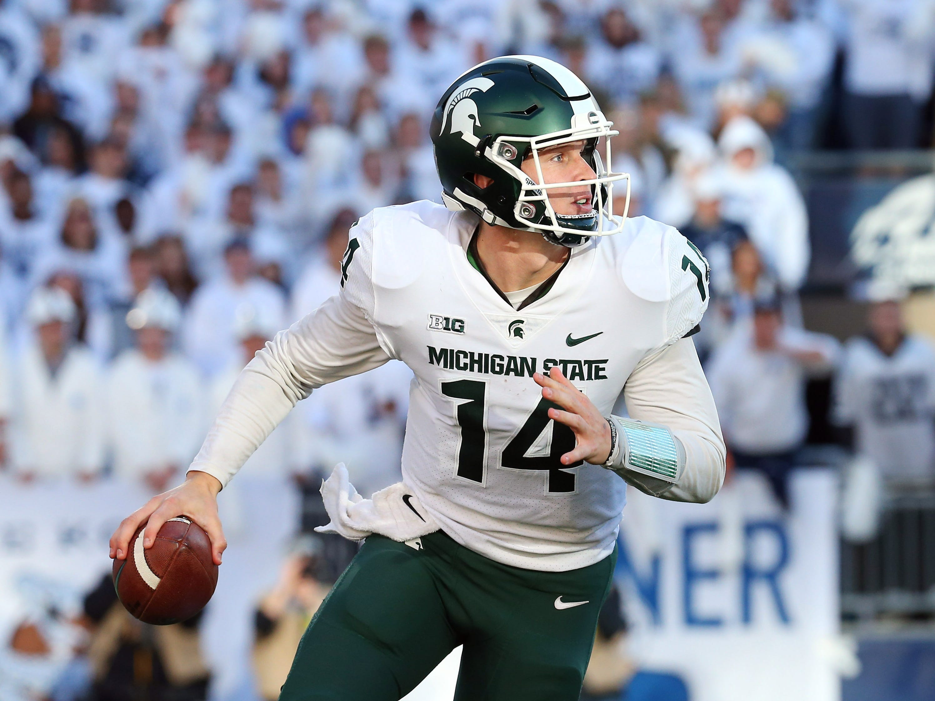 Michigan State Spartans quarterback Brian Lewerke (14) runs with the ball against the Penn State Nittany Lions during the second quarter at Beaver Stadium.