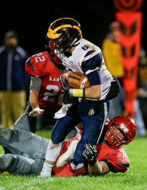 Manitowoc Lutheran's Alex Sprenger (75) tackles Ozaukee's quarterback Brent Hoffman (6) during a Big East Conference matchup Friday in Manitowoc.