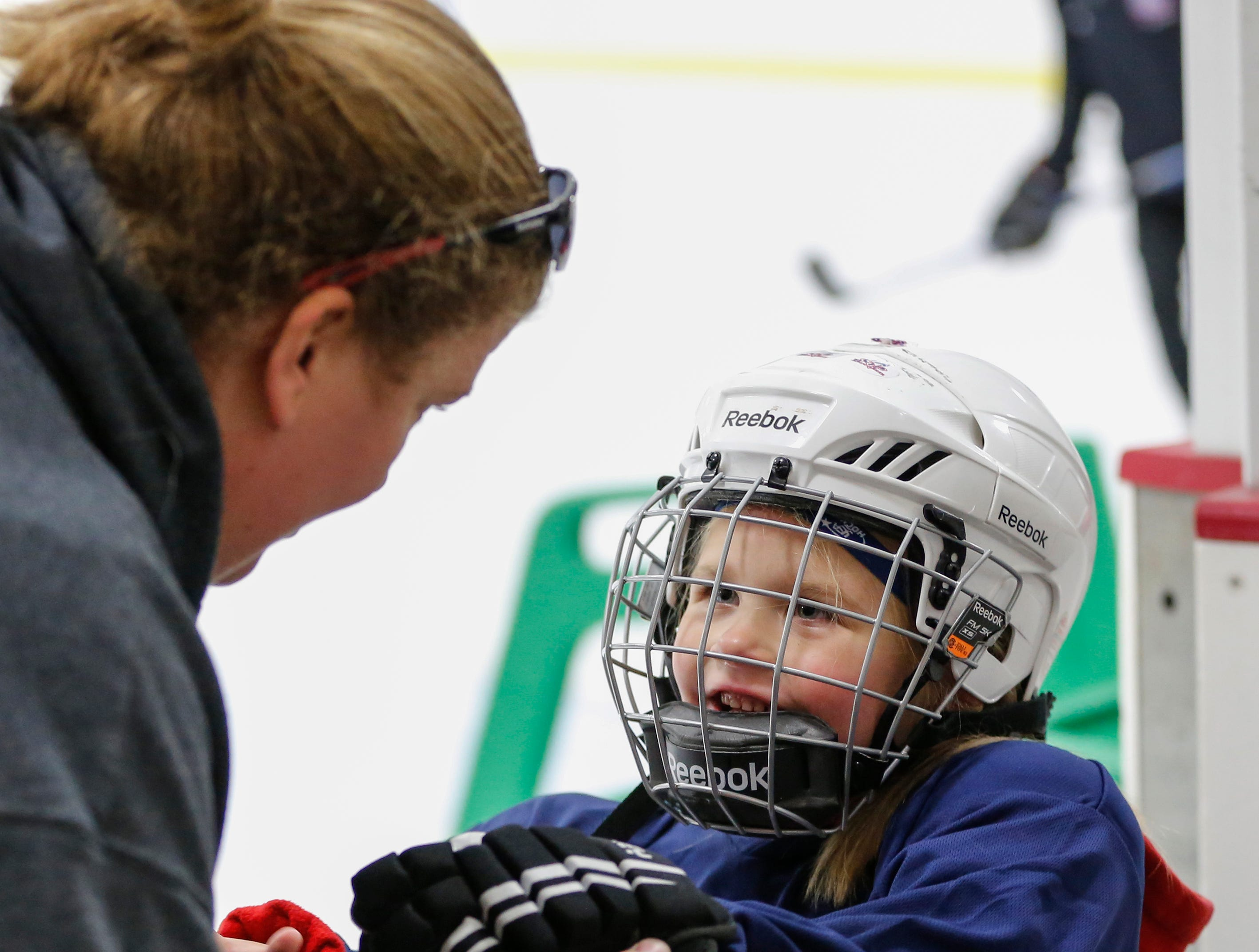 Cassidy Schloseky helps her daughter Zoe, 4, with her glove as she hits the ice for the first time during the Girls Try Hockey event at the County Ice Center Saturday, October 13, 2018, in Manitowoc, Wis. The Joshua Clark/USA TODAY NETWORK-Wisconsin