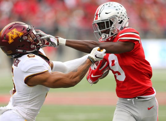 Ohio State wide receiver Ben Victor tangles with Minnesota defensive back Chris Williamson during the second quarter at Ohio Stadium.