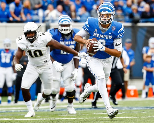 Memphis quarterback Brady White (right) scrambles past the Central Florida defense during action in Memphis, Tenn., Saturday, October 13, 2018.