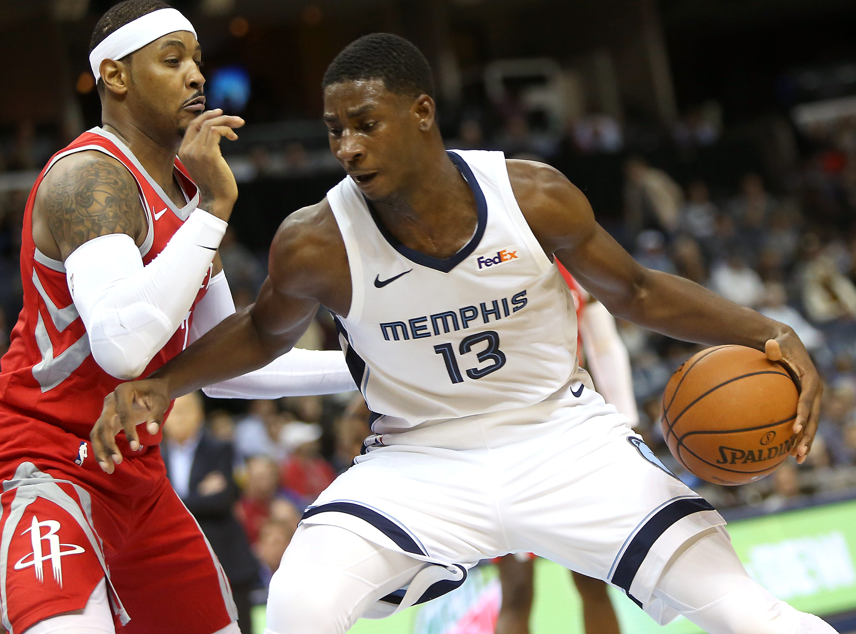 Memphis Grizzlies Jaren Jackson Jr. pounds the ball inside against Houston Rockets defender Carmelo Anthony during preseason action at the FedExForum in Memphis, Tenn., Friday, October 12, 2018.