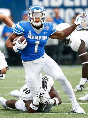 Memphis running back Tony Pollard runs past Central Florida defender Eriq Gilyard on Saturday.