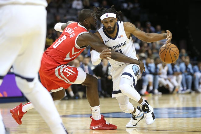 The Grizzlies' Mike Conley is stripped and fouled by the Rockets' James Ennis III during a preseason game Oct. 12.