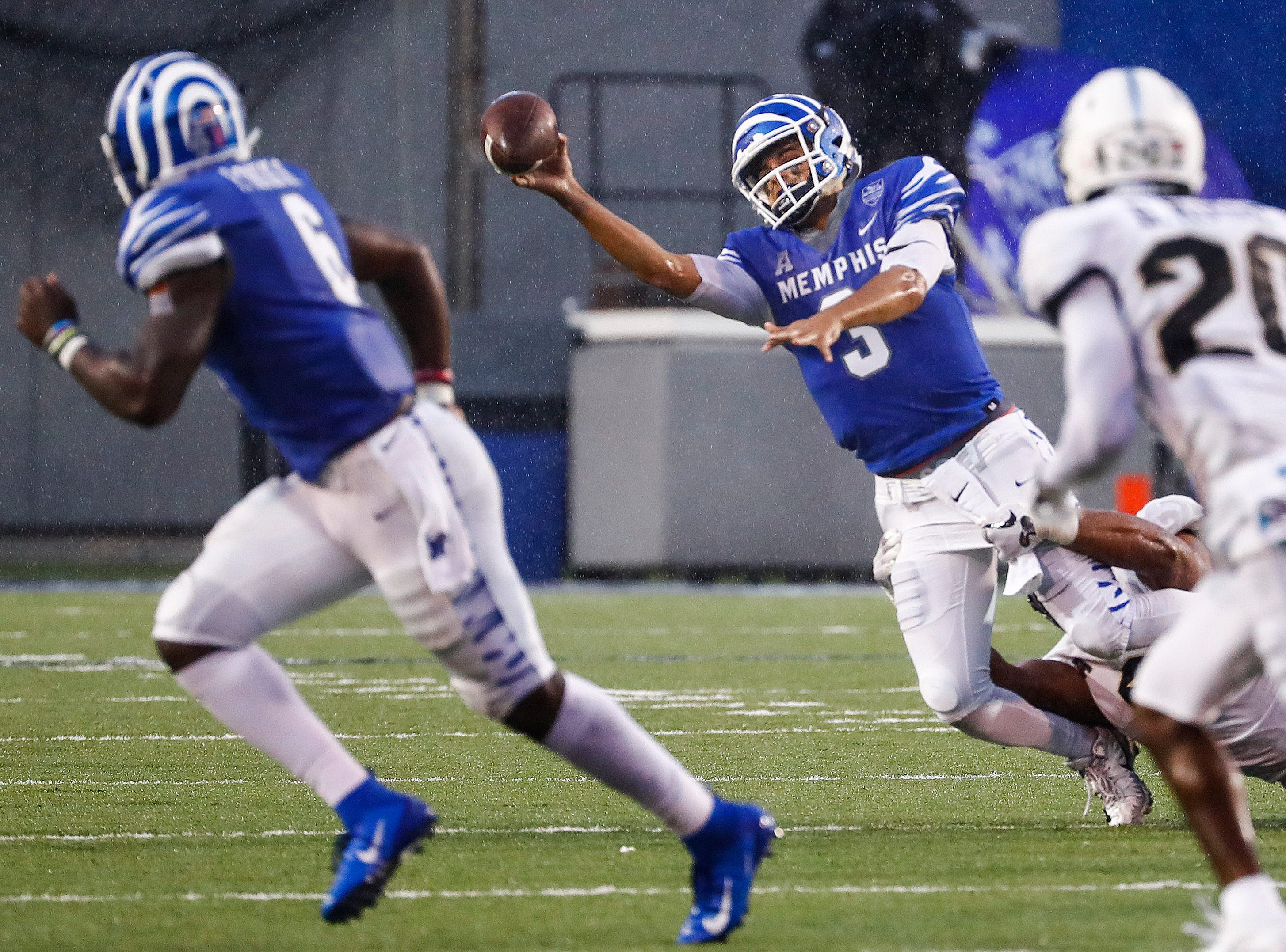 Memphis quarterback Brady White (middle) makes a throw before being sacked by Central Florida during action in Memphis, Tenn., Saturday, October 13, 2018.