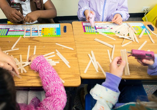 A group of four girls build bridges out of popsicle stick as a part of an engineering workshop at Hutchinson School during the Strong GIRL Fest Saturday October 13, 2018.