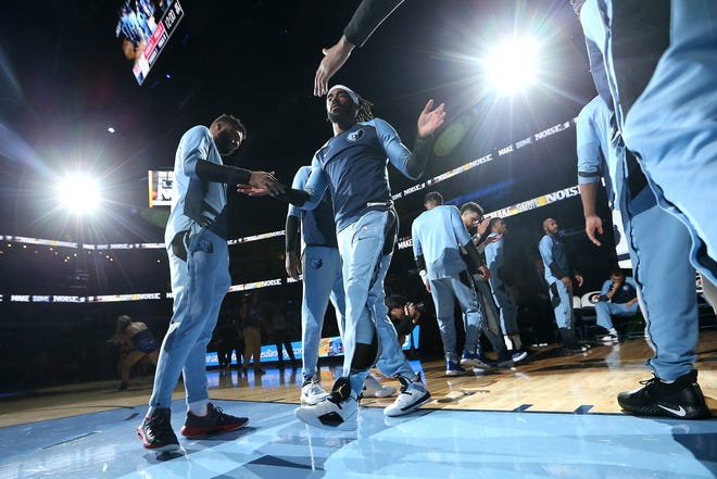 Memphis Grizzlies Mike Conley high-fives teammates before they take on the Houston Rockets for a preseason game at Memphis, Tenn., Friday, October 12, 2018.