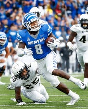 Memphis running back Darrell Henderson (top) runs past  Central Florida defender Kyle Gibson (bottom) for a touchdown during acton in Memphis, Tenn., Saturday, October 13, 2018.