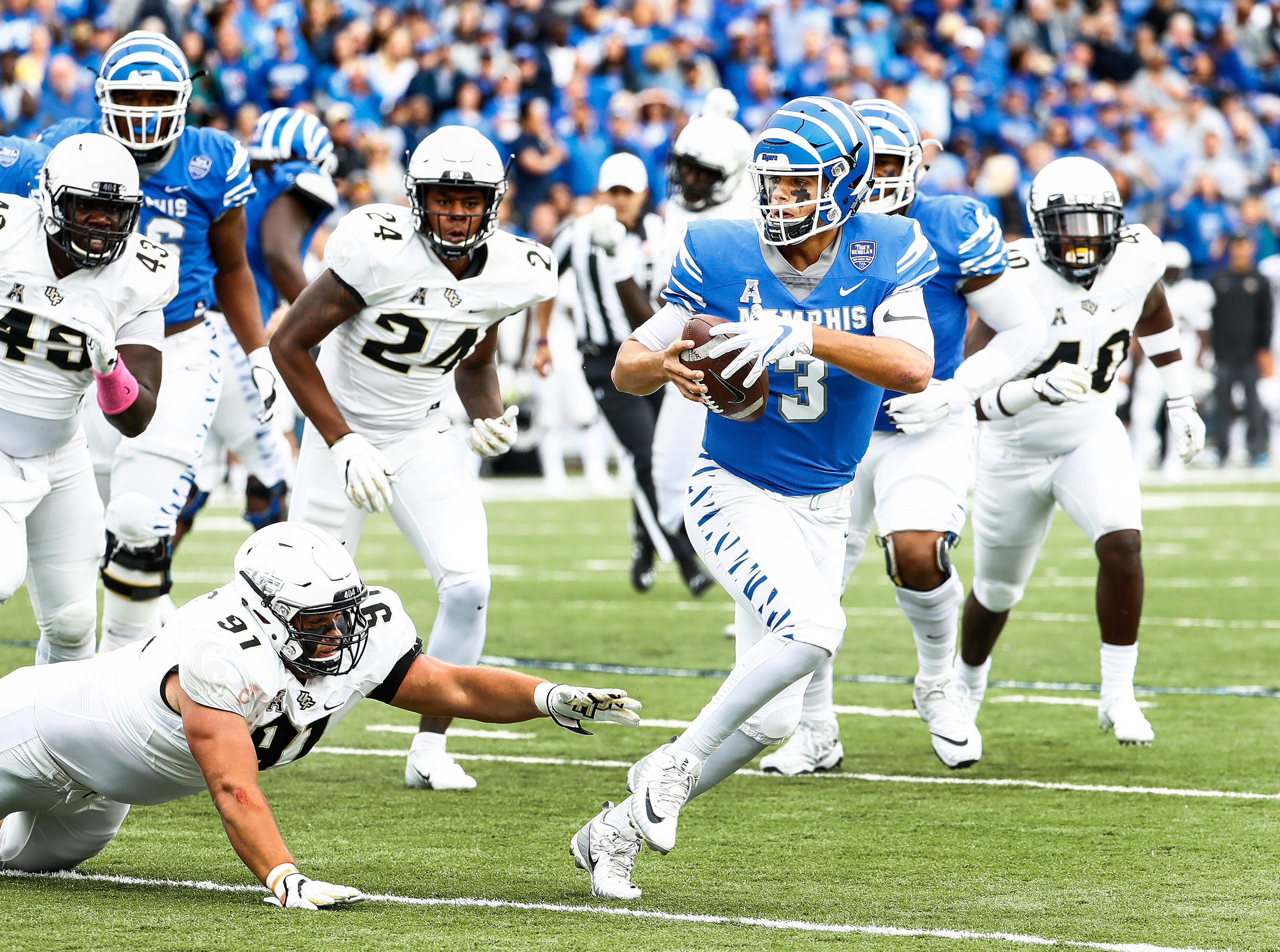 Memphis quarterback Brady White (right) scrambles past the Central Florida defense for a touchdown during action in Memphis, Tenn., Saturday, October 13, 2018.