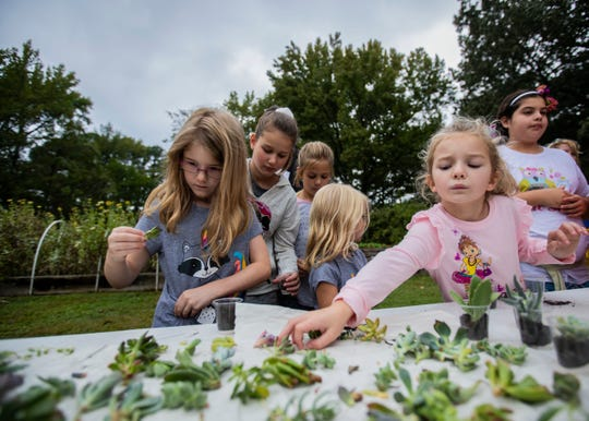"""A group of girls participate in the """"Build Your Own Terrarium"""" station at the Strong GIRL Fest Saturday."""