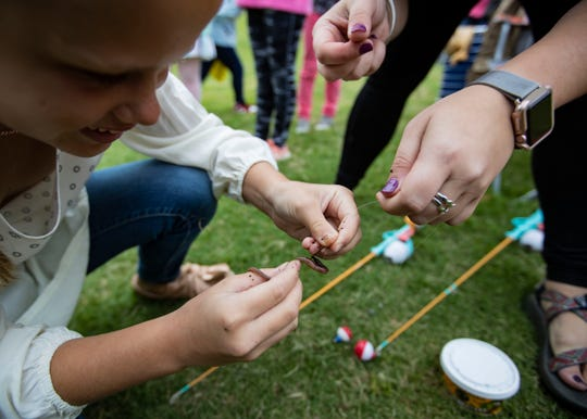 Andrea Jeter, SPARK assistant teacher, teaches Marybrooks Winchester how to bait a hook at the Strong GIRL Fest Saturday.