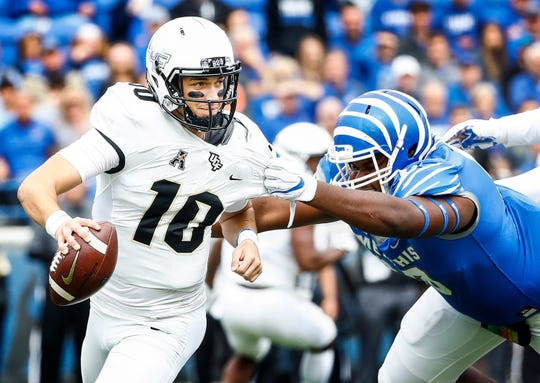 Memphis defender John Tate IV (left) sacks Central Florida quarterback McKenzie Milton (right) during action in Memphis, Tenn., Saturday, October 13, 2018.