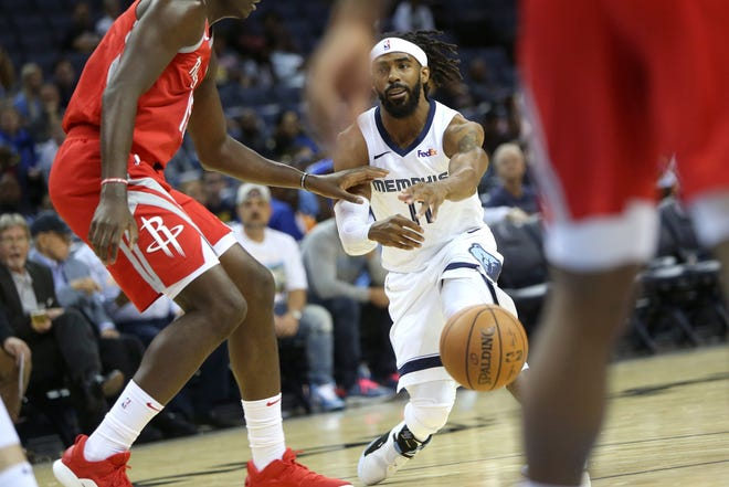 Memphis Grizzlies 	Mike Conley squeezes a bounce pass between Houston Rockets defenders during preseason action at the FedExForum in Memphis, Tenn., Friday, October 12, 2018.