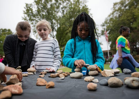 """A group of girls construct bridges out of rocks wide enough for a toy car the go under at the """"Building Bridges with Rocks Stations"""" workshop at Hutchinson School during the Strong GIRL Fest Saturday."""