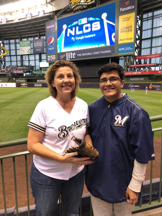 Cindy Rogers is ready to catch a fly ball at the Brewers' first NLCS game against the Los Angeles Dodgers on Oct. 12, 2018. Her son Matthew Rogers (right) has backup.
