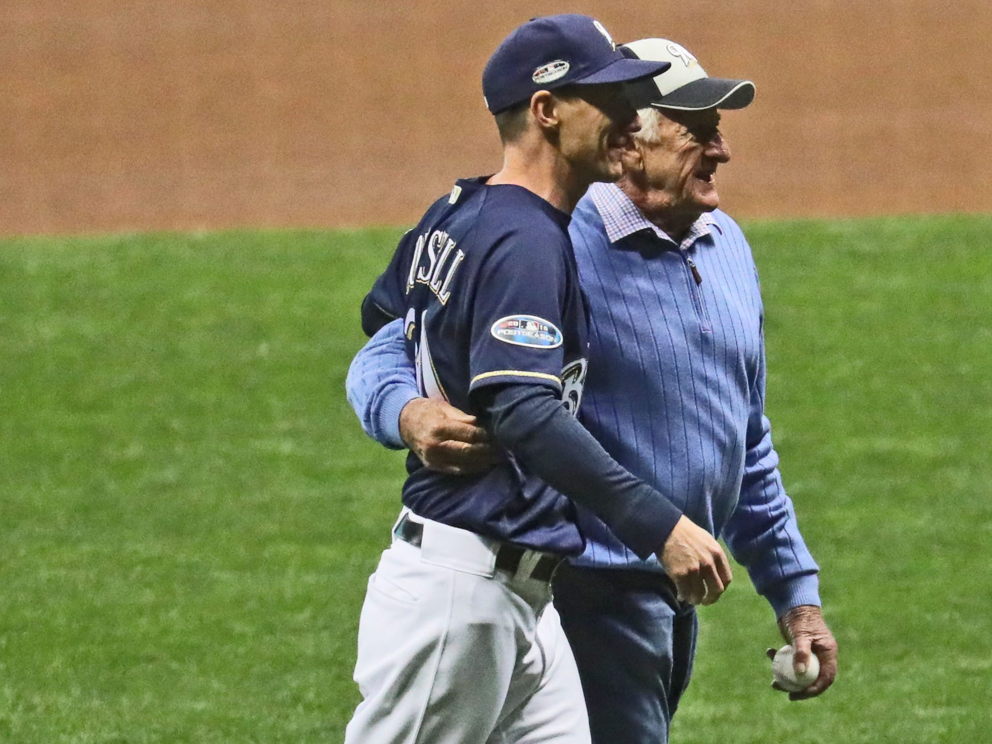 Brewers manager Craig Counsell walks Bob Uecker back to the dugout after Uecker threw out the first pitch.