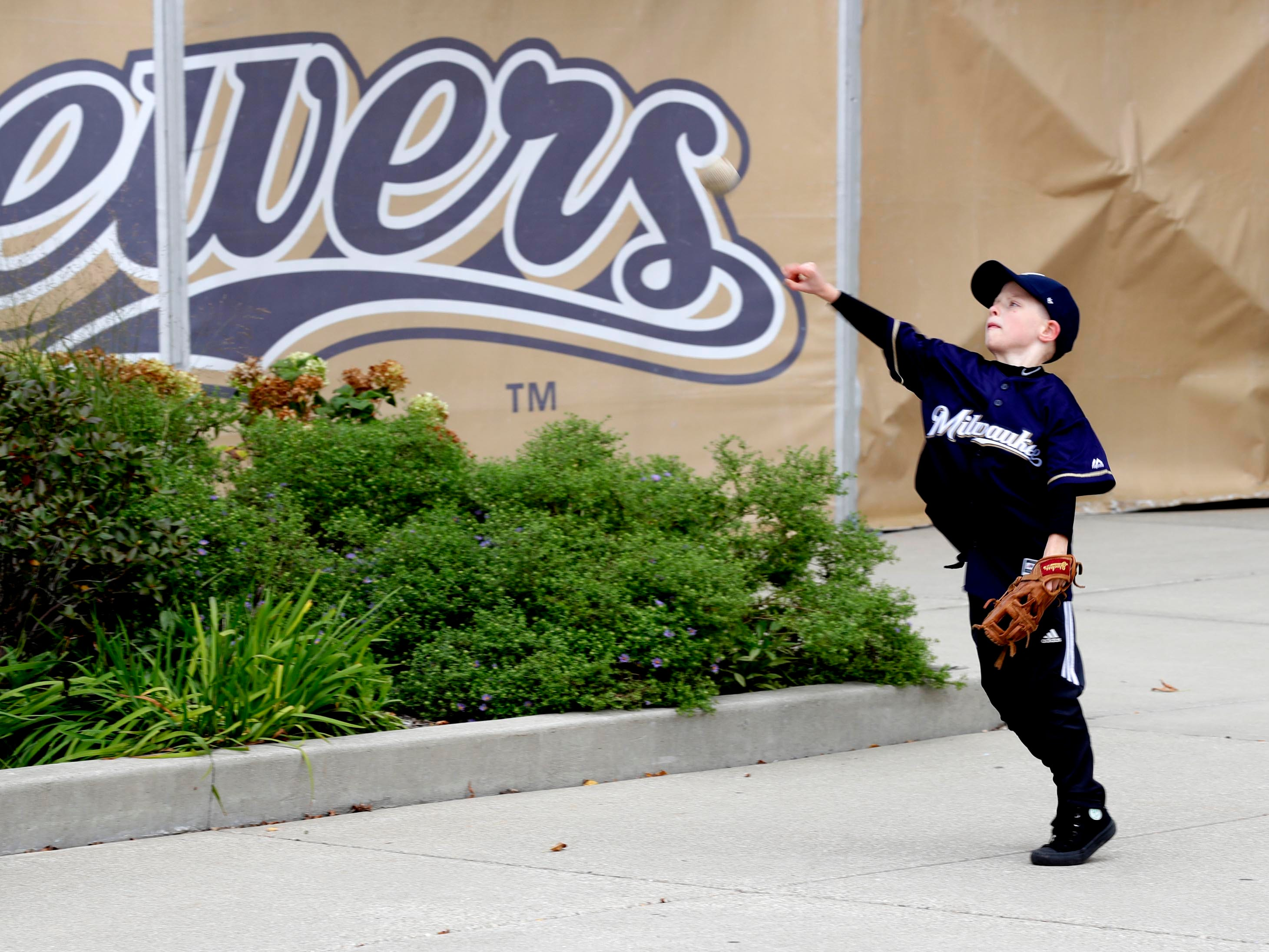 Rylan Hahn, 6, of Hazelgreen practices his pitching with family before the game.