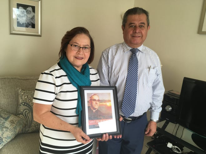 Letitia and Carlos Barilla hold an image of Archbishop Oscar Romero, who will be declared a saint by Pope Francis on Sunday. Romero, a champion of the poor and critic of both sides, was assassinated by a gunman linked to a right wing death squad in El Salvador in 1980.