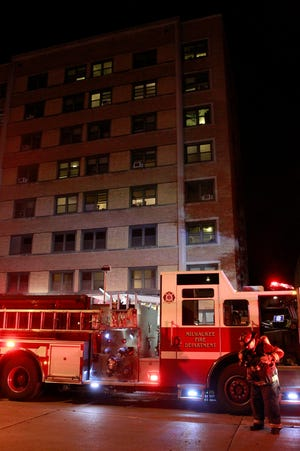 A firefighter is seen at the scene of an apartment fire at 1032 E. Knapp St., Milwaukee, on Friday.