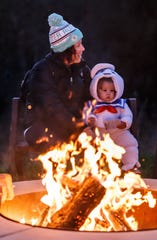 Marlo Johnson of Waukesha, Wisconsin and her one-year-old daughter Paisley enjoy the warmth of a bonfire during Howl-O-Ween at Retzer Nature Center in Waukesha on Oct. 12, 2018.