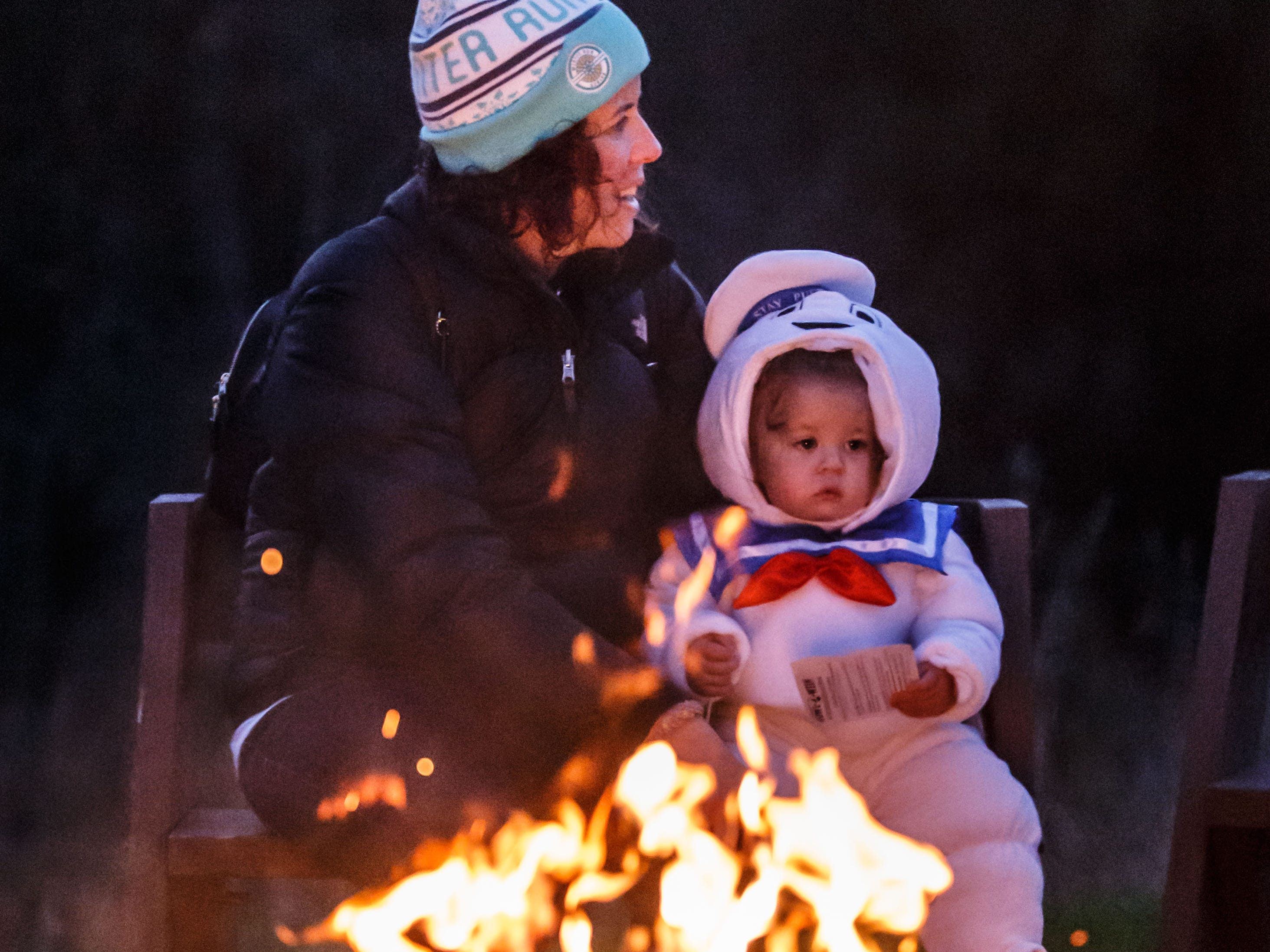 Marlo Johnson of Waukesha and her one-year-old daughter Paisley enjoy the warmth of a bonfire during Howl-O-Ween at Retzer Nature Center in Waukesha on Friday, Oct. 12, 2018. The family friendly event featured night hikes, children's games, a DJ dance party, planetarium shows, a campfire and more.