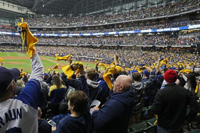 Fans cheer as the Brewers take the field  for NLCS Game 1 at Miller Park.
