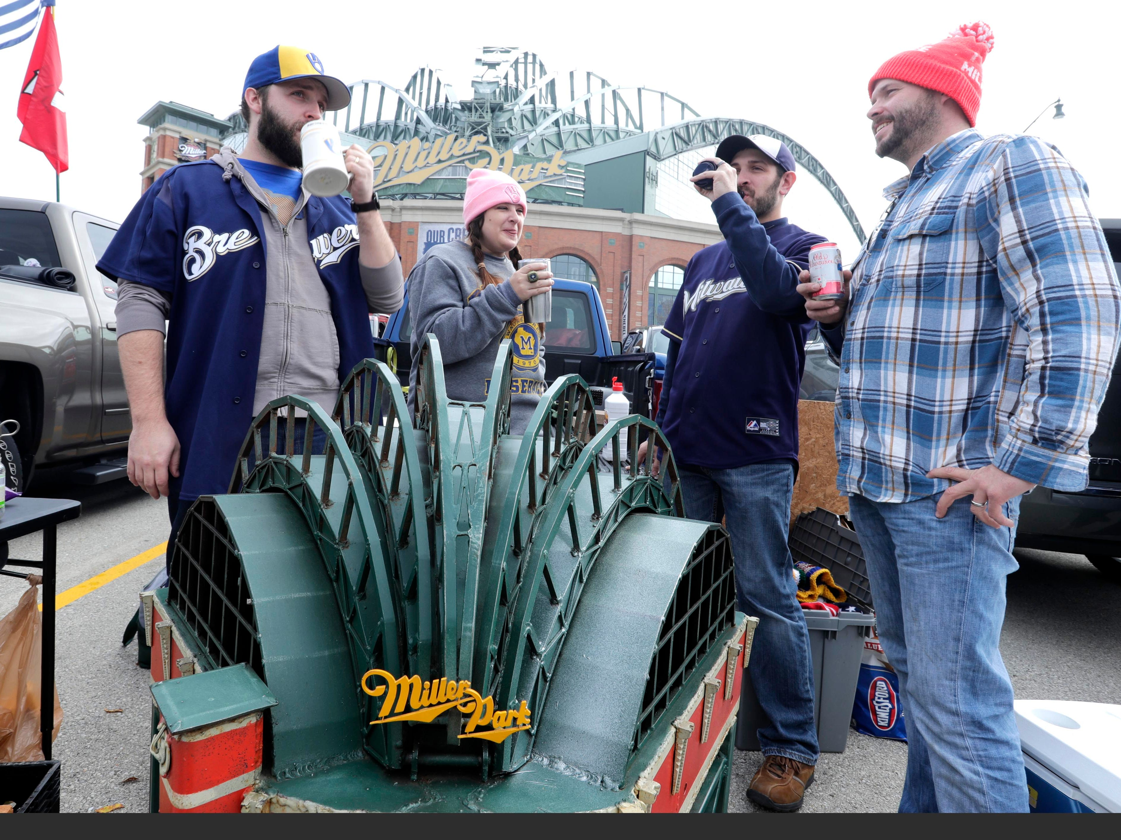 Dylan Brown (from left), Brittany Brown, Josh Jenswold and Evan Olson enjoy their beverages as they tailgate Saturday with a steel replica of Miller Park made three years ago by their friend Matt Tyler. They were at Miller Park for Game 2 of the National League Championship Series between the Milwaukee Brewers and Los Angeles Dodgers.